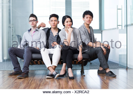 Young office workers sitting in a sofa - Stock Photo