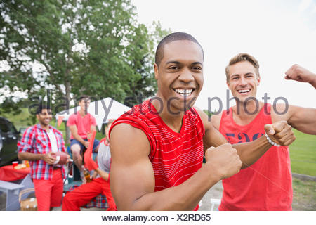 Men flexing muscles at tailgate barbecue in field - Stock Photo