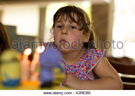 Girl blowing out candles  on her birthday cake - Stock Photo