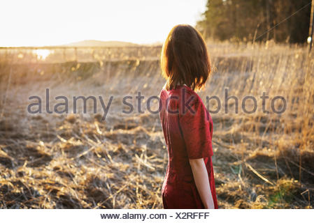 Finland, Varsinais-Suomi, Young woman standing in field - Stock Photo