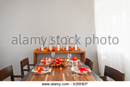 Dinner table setting in warm orange red autumn colors - Stock Photo