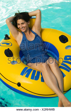 Woman lying on inflatable raft in swimming pool, elevated view. - Stock Photo