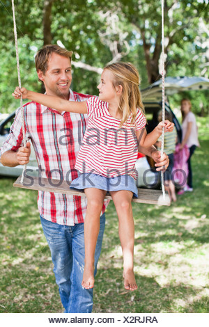 Father pushing daughter on swing - Stock Photo