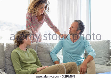 Family having a discussion in living room at home - Stock Photo