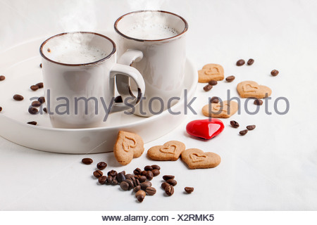 Two cups of cappuccino served with spices and cookies as hearts and one red heart on white textile. - Stock Photo
