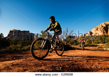 Two middle age men ride mountain bikes through the red rock country of Sedona, AZ. - Stock Photo