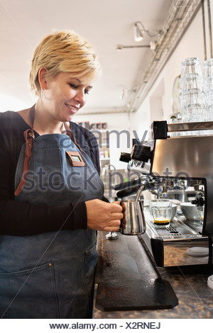 Barista heating up milk using coffee machine - Stock Photo