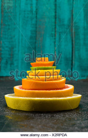 close up view of different fresh citrus fruits slices on blue - Stock Photo