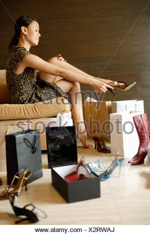 Woman putting on high heel shoes, surrounded by shopping bags, shoes boxes and shoes - Stock Photo