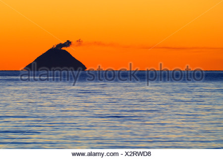 Smoke coming from Mt. Augustine Volcano (Ring of Fire) at sunset, picture taken from ca 140 km away, Kenai Peninsula, Alaska, U - Stock Photo