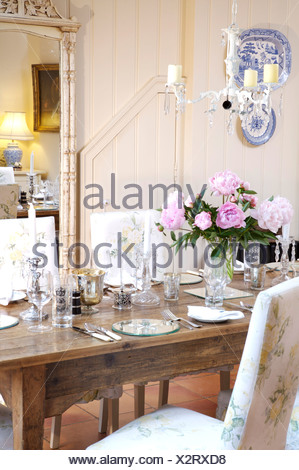 an oak table set for 6 in a large dining room adjacent to