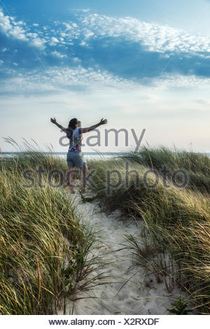 Woman rejuvenated by the coastal outdoors of Cape Cod, Massachusetts, USA - Stock Photo