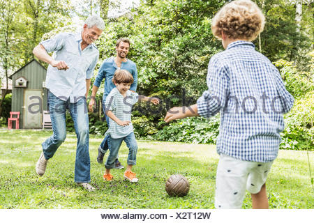 Mid adult man with father and sons playing garden soccer - Stock Photo