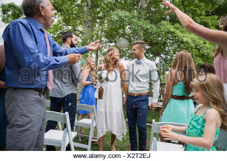 Guests throwing confetti over bride groom backyard wedding - Stock Photo