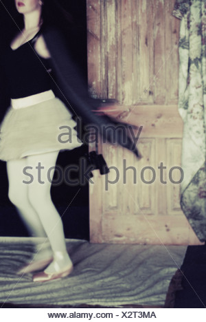 A young woman wearing a white short skirt and black jacket spinning around - Stock Photo