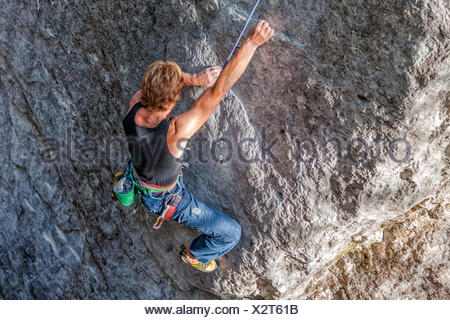 Free climbing, rock climbing in natural cliff. Climber in action on a rock path equipped. Gares, Dolomites, Veneto, Italy - Stock Photo