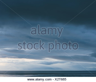 The sea and sky over Puget Sound in Washington USA The horizon with light and cloud layers above Gathering storm clouds - Stock Photo