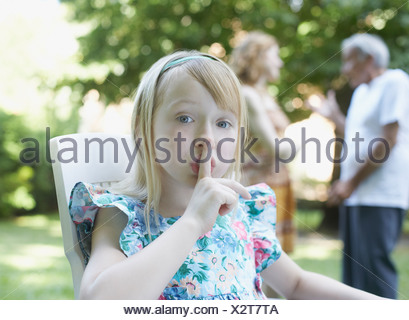 Young girl sitting outdoors with finger to lips shushing - Stock Photo