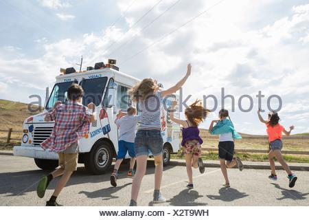 Group of children running towards ice cream truck - Stock Photo