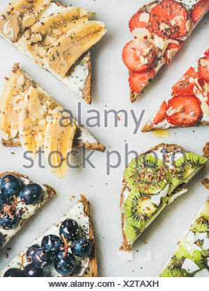 Healthy breakfast toasts cut in pieces. Wholegrain bread slices with cream cheese, various fruit, seeds and nuts. Top view, grey marble background. Cl - Stock Photo
