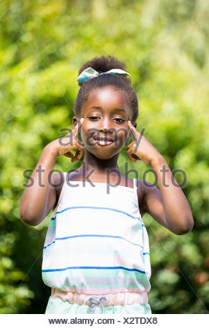 Mixed-race girl grimacing face to the camera - Stock Photo