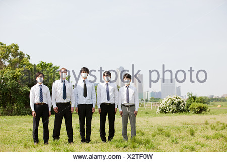 Businessmen in a row wearing pollution masks - Stock Photo