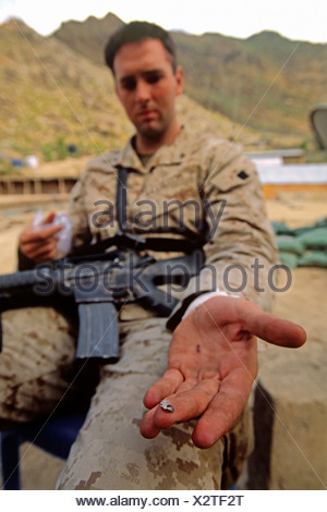 A US Marine Shows off a Piece of a Bullet Removed from His Wrist after a Firefight - Stock Photo