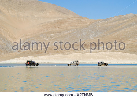 Three SUVs on an eye land in Pengong tso Lake ( an endorheic lake in the , situated at a height of about 4,350 m (14,270 - Stock Photo