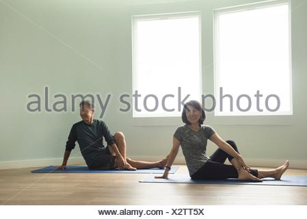 Mature couple sitting on yoga mat leaning on hand, legs crossed looking away smiling - Stock Photo