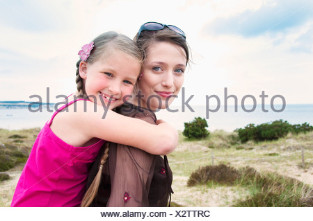 Mother carrying daughter piggy back - Stock Photo