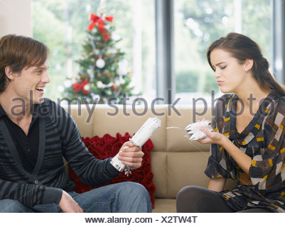 Woman disappointed by short end of Christmas cracker - Stock Photo