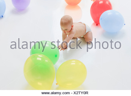 Baby reaching for balloons on floor - Stock Photo