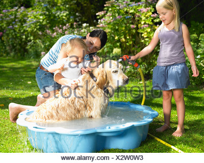 Mother, daughter and son washing the dog - Stock Photo