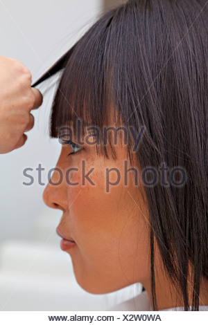 Side view of Asian woman getting a new haircut - Stock Photo