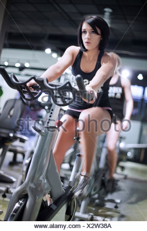 A young woman rides a stationary bike in a fitness gym.  Head in focus and legs motion blurred. - Stock Photo