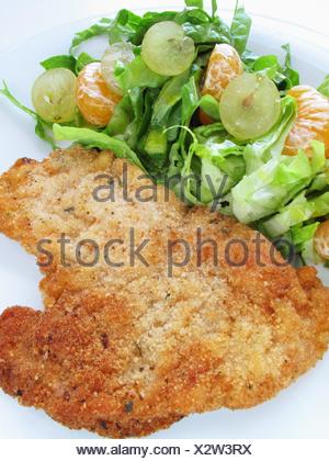 Breaded chicken fillet with fruit salad - Stock Photo