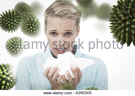 Composite image of blonde sick woman holding lots of tissues - Stock Photo
