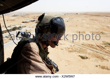 US Marine flight crew chief scans desert below Marine Corps UH-1N utility helicopter fitted weapons during combat operation - Stock Photo