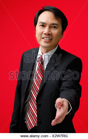 A businessman extends his hand to shake hands - Stock Photo