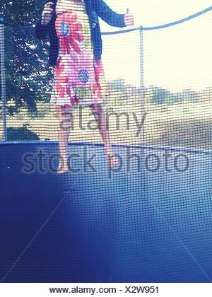 Low Section Of A Woman Jumping On Trampoline Against Landscape - Stock Photo