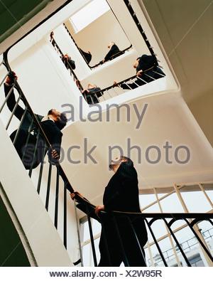 Businessmen walking up spiral stairway - Stock Photo