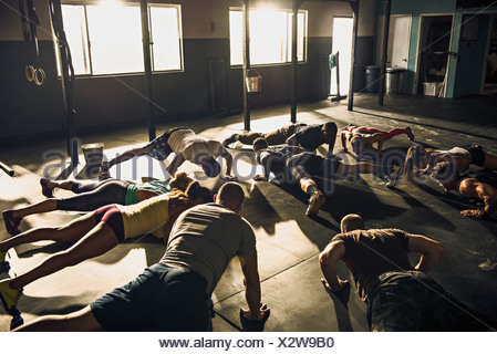 Fitness group doing push ups in gym - Stock Photo