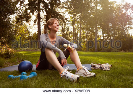 Mid adult woman sitting in park taking exercise break - Stock Photo