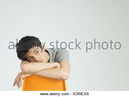 Young man sitting, leaning head on back of chair - Stock Photo