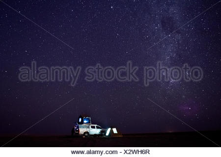 camper van with tent on the roof and the milky way - Stock Photo