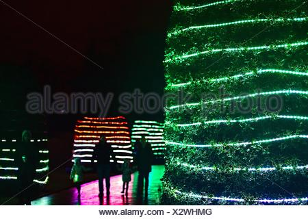 People Walking On Footpath By Illuminated Christmas Decorations At Night - Stock Photo