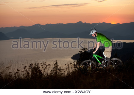 Young adult mountain biking at sunrise in Idaho. - Stock Photo