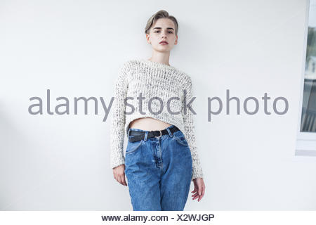 Portrait of a blonde woman leaning against a wall - Stock Photo