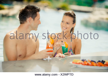 Young couple in swimming  pool having a cocktail together, Dubrovnik, Croatia - Stock Photo