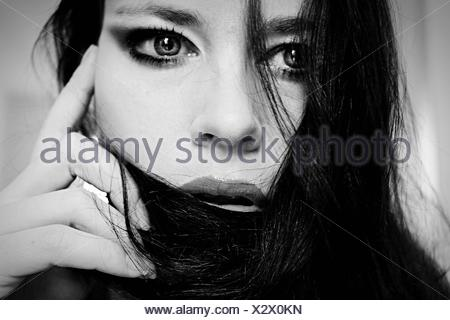 Close-Up Of Thoughtful Young Woman Covering Face With Hair - Stock Photo